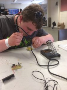 An Explorer Scout busy building a transistor radio kit